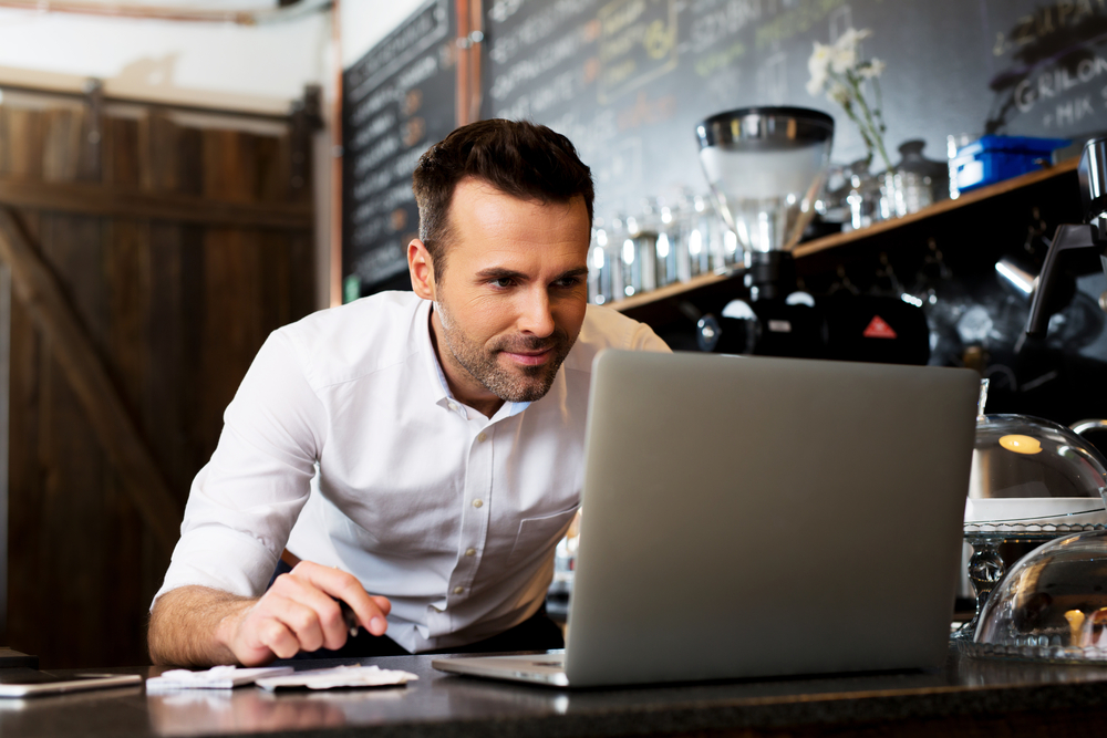 Man working in coffee shop looking at a computer