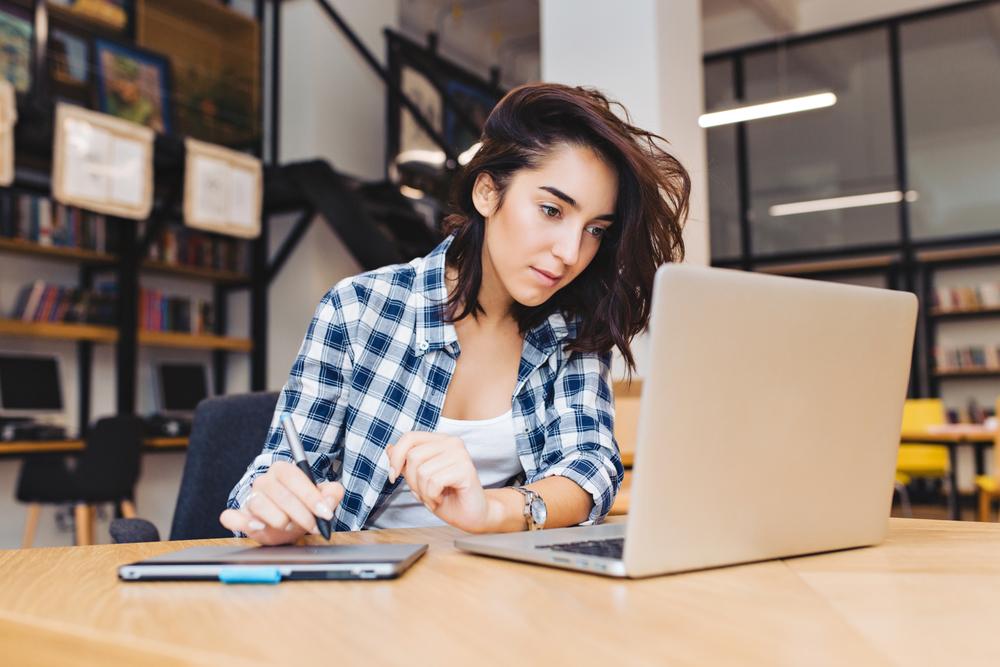 Female freelancer works on project on laptop