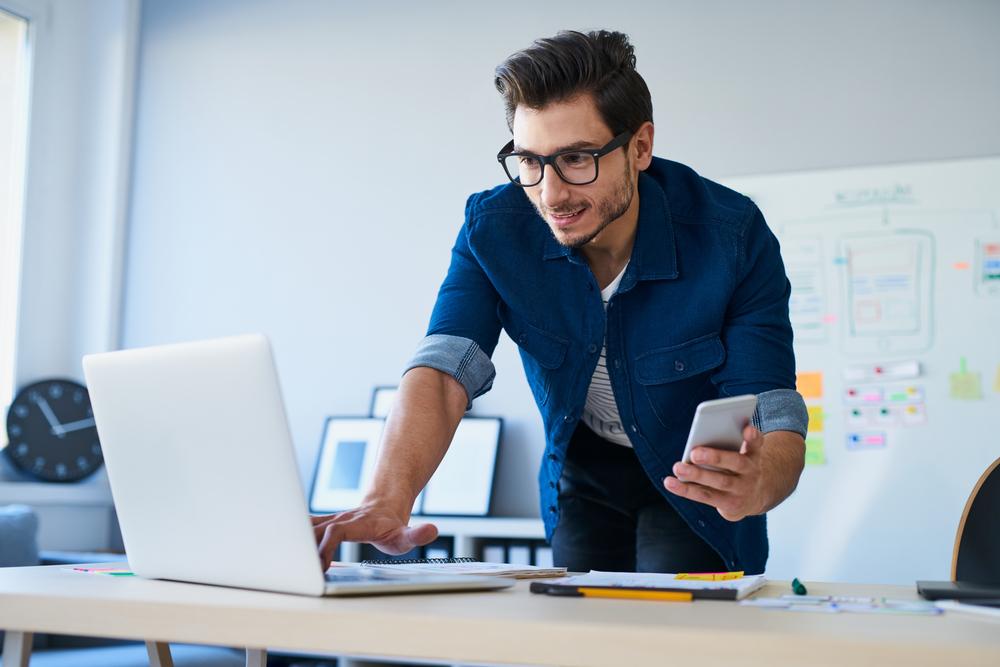 Man wearing glasses checks computer