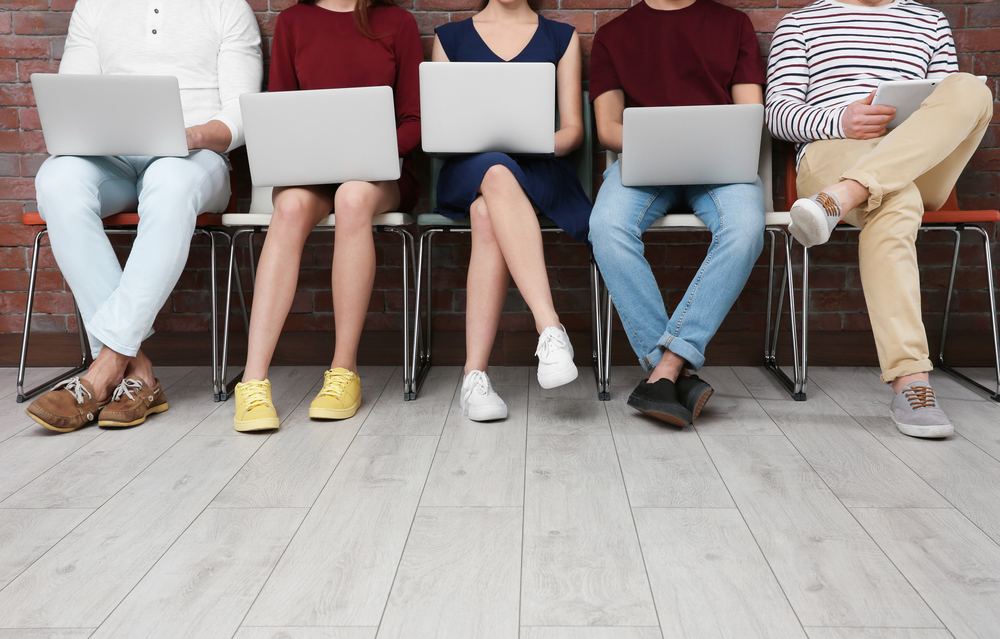 Group of freelancers work on laptops side by side