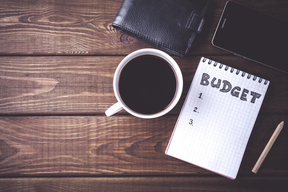 Budget sheet on table next to a mug of coffee