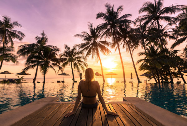 A-woman-relaxes-by-a-pool-on-vacation-in-front-of-a-beautiful-sunset.