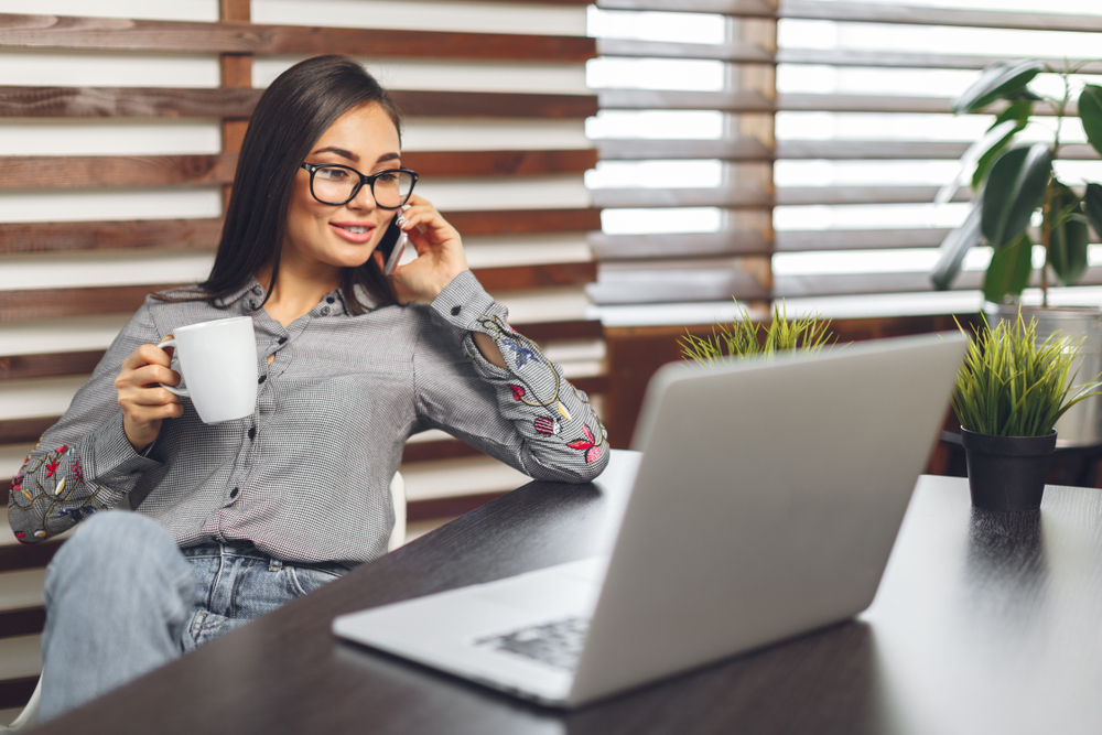 A-laid-back-woman-smiles-at-her-desk-while-drinking-coffee-and-wearing-glasses